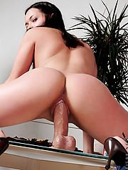 Sweet Valeska thrusting her wet dripping pussy with a realistic cock dildo on top of the table