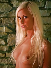 Stunning blonde beauty tied up naked in a creepy dungeon