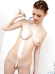 Nubile ally drops lotion on her boobies and watches it coat her nipples and stomach