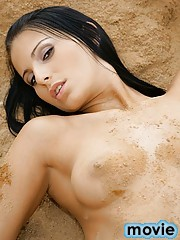 Stunning brunette beauty goes naked in a sandy land dune