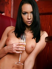 Erotic brunette babe with a glass of bubbles posing nude