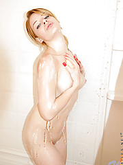 Totally naked Allyann drills her shaved pink pussy with a glass dildo inside the bathroom
